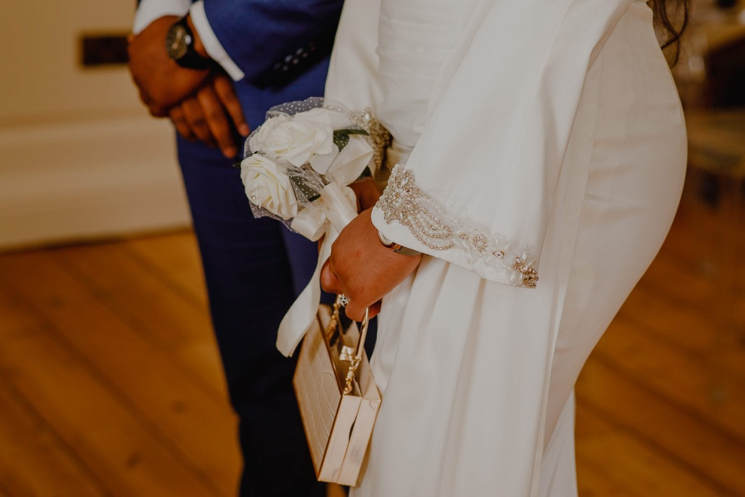 Bride holds her wedding bad and bouquet.