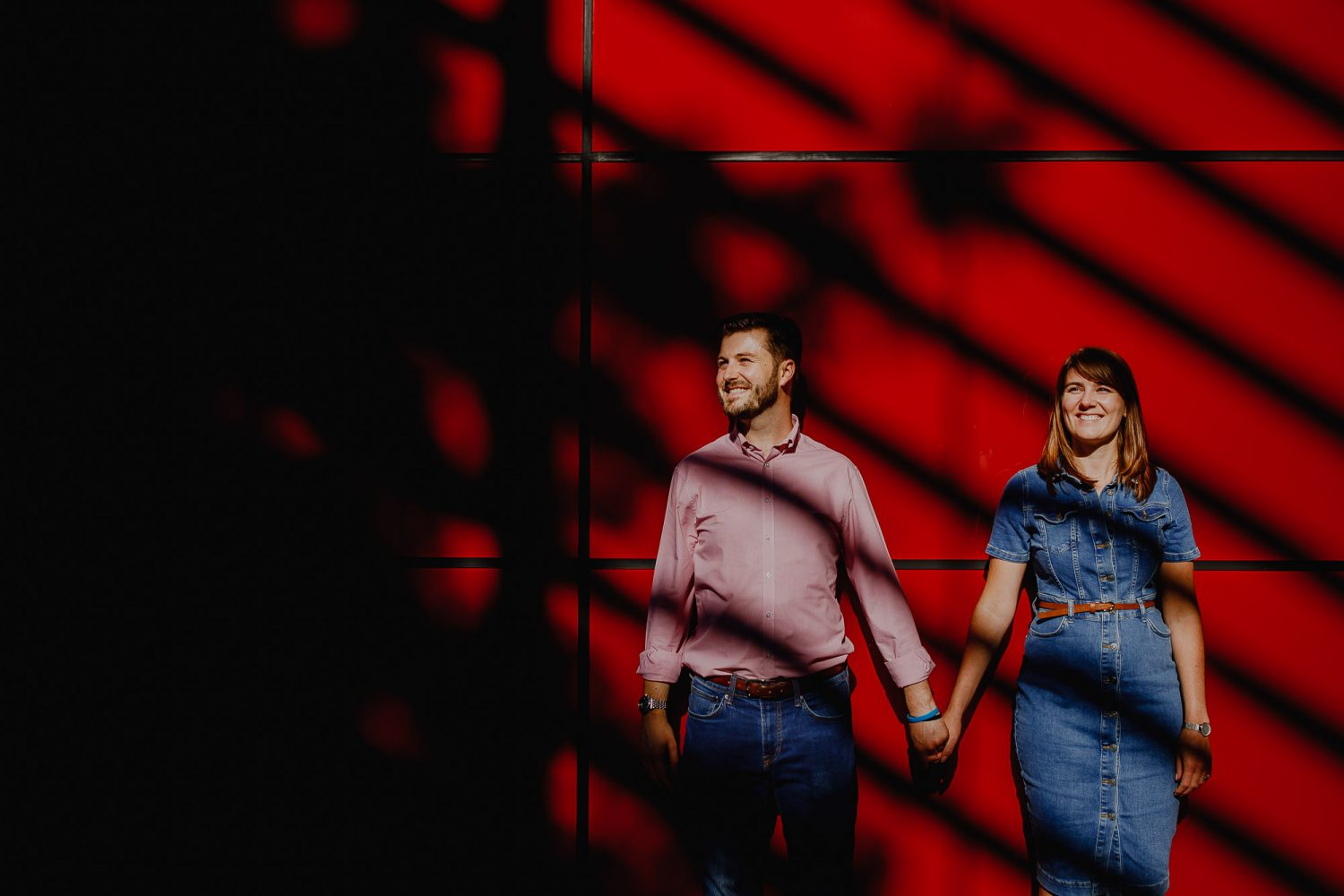 London pre-wedding portrait of couple against a vibrant red wall.